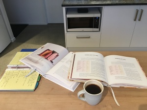 Cookbooks and coffee spread out on a table